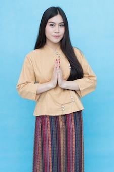 Ritratto della ragazza asiatica nella preghiera tailandese tradizionale del vestito