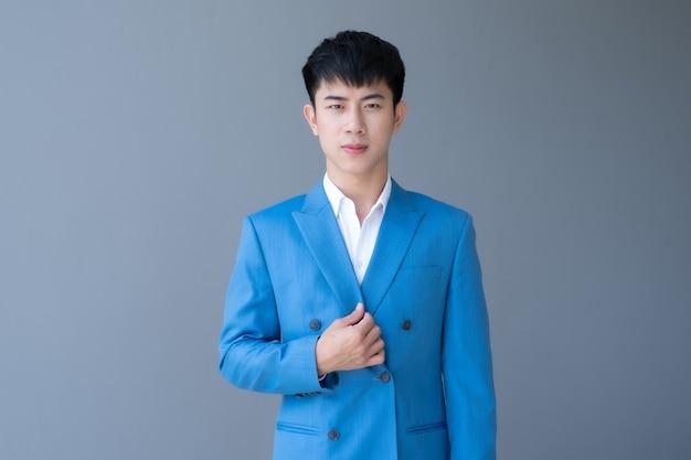 Ritratto di giovane uomo bello asiatico in vestito blu su grigio