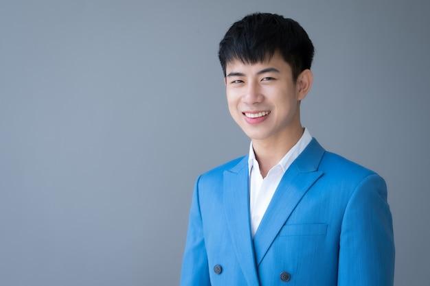 Ritratto di giovane uomo bello asiatico in vestito blu che sorride sul grigio