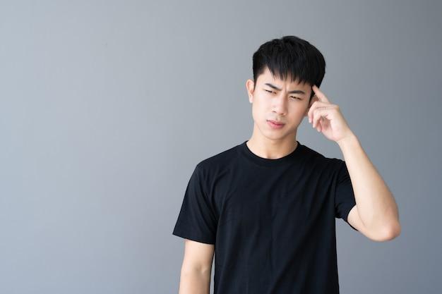 Ritratto di giovane uomo bello asiatico su grigio