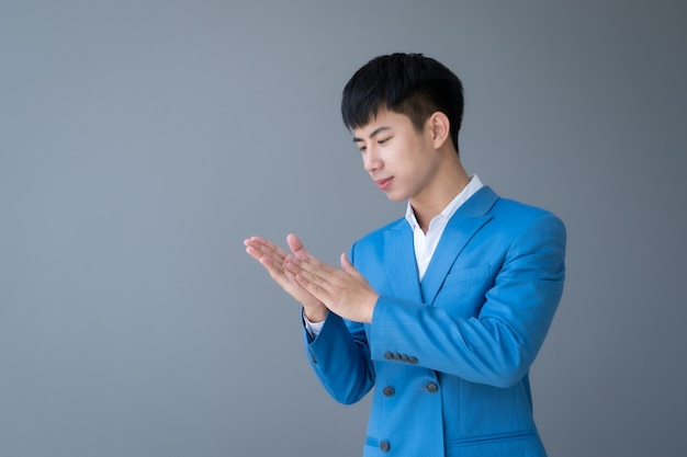 Ritratto di asiatico giovane uomo bello lavare a mano su grigio