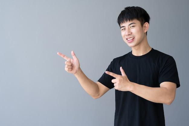 Ritratto di giovane uomo bello asiatico sorridente sul grigio