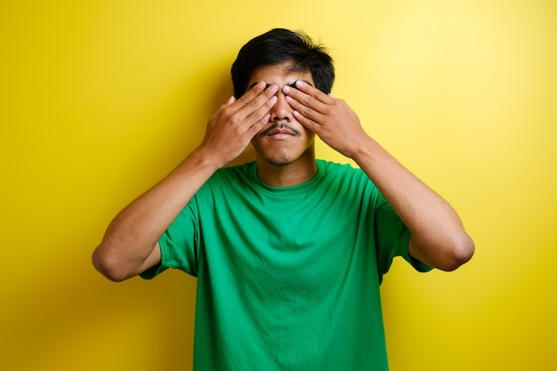 Ritratto di giovane asiatico in maglietta verde che copre gli occhi con entrambe le mani su sfondo giallo