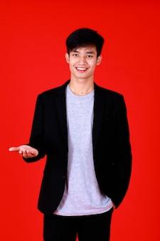 Ritratto di giovane asiatico che indossa t-shirt grigia e abito nero. guardare in piedi la macchina fotografica con un sorriso sul viso sembrare felice e fiducioso. la mano destra allunga la mano e il palmo rivolto verso l'alto per tenere il prodotto a portata di mano.