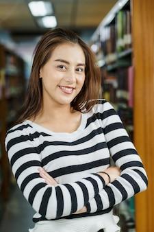 Ritratto di giovane studente asiatico in abito casual in biblioteca di università o college su sfondo scaffale