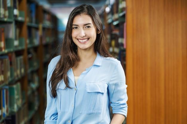 Ritratto di giovane studente asiatico in abito casual in biblioteca di università o college su scaffale, apprendimento e istruzione, torna al concetto di scuola e università