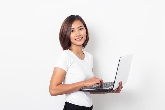 Computer portatile asiatico della tenuta della giovane donna del ritratto isolato