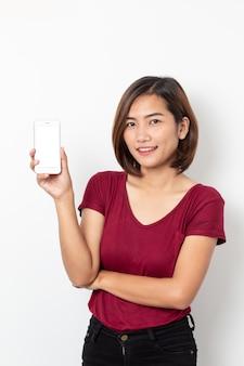 Smartphone asiatico della tenuta della giovane donna del ritratto isolato