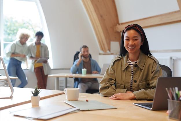 Ritratto di giovane donna asiatica che sorride alla macchina fotografica mentre lavora al suo posto di lavoro con altre persone