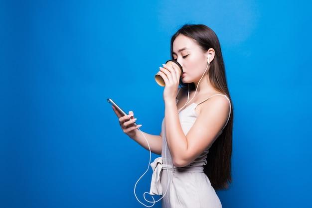 Ritratto di giovane donna asiatica in piedi sorriso, utilizzando il telefono cellulare la sua azienda tazza di carta da caffè, guardando smartphone sulla parete blu
