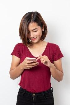 Giovane donna asiatica del ritratto che utilizza smartphone isolato su bianco