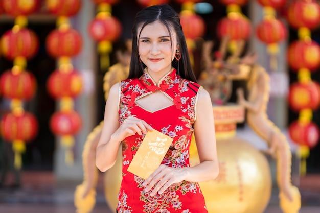 Ritratto di giovane donna asiatica che indossa rosso cheongsam cinese tradizionale, che tiene buste gialle con il testo cinese blessings scritto su di esso è una buona fortuna per il capodanno cinese