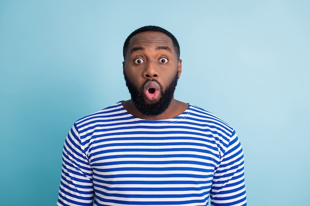 Ritratto di stupito ragazzo afroamericano sembra incredibile novità impressionato urlo indossare abbigliamento nautico marinaio isolato sopra la parete di colore blu