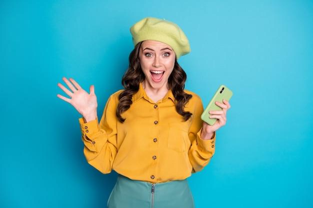 Ritratto di stupita ragazza pazza allegra usa smartphone impressionato commento positivo sui social network urla wow omg indossa vestiti gialli copricapo isolati su sfondo blu