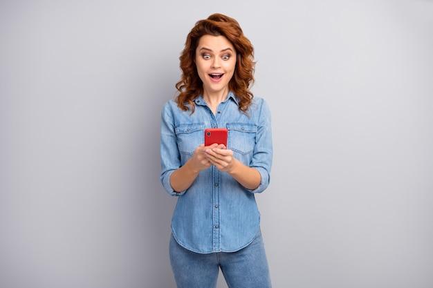 Ritratto di stupito folle tossicodipendente donna usa smartphone leggere social media novità impressionato urlo wow omg indossare vestito elegante isolato sopra la parete di colore grigio