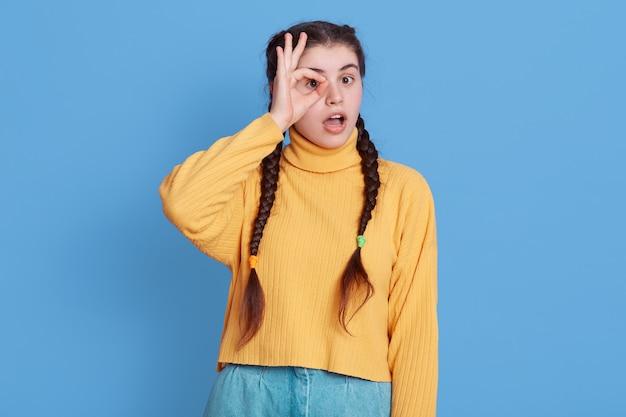 Il ritratto della ragazza europea pazza stupita fa bene e firma l'occhio del binocolo, rimanendo impressionato, fissando davanti con la bocca aperta, indossa un pullover giallo isolato sopra la parete di colore blu