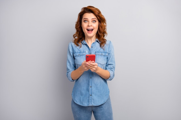 Ritratto di donna pazza stupita utilizzare il telefono cellulare leggere novità sui social media impressionato urlo wow omg indossare un bell'aspetto vestito isolato su grigio muro