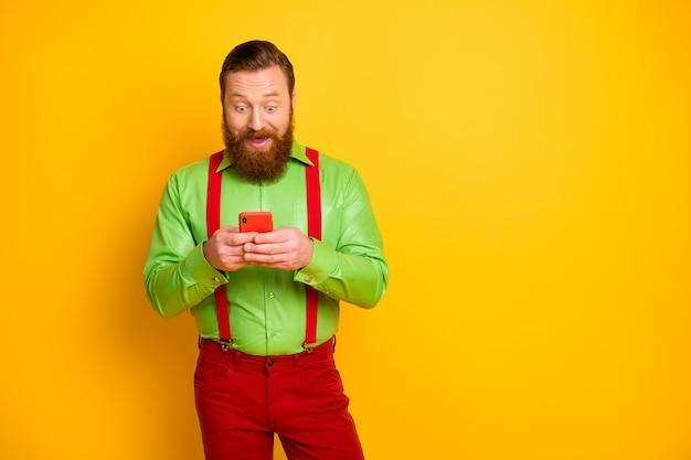 Ritratto di blogger uomo eccitato stupito uso cellulare leggere informazioni di social network urlo impressionato wow omg indossare pantaloni bretelle pantaloni isolati su colore giallo