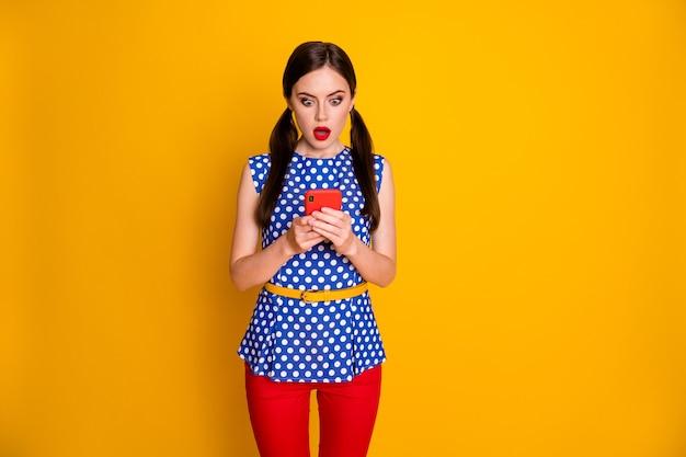 Il ritratto di una ragazza stupita usa il cellulare impressionato dalle informazioni sul virus corona del social network indossa pantaloni alla moda isolati su uno sfondo di colore brillante brillante
