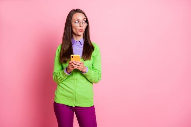 Il ritratto della ragazza stupita usa lo smart phone guarda copyspace indossa pantaloni pantaloni isolati sfondo color pastello