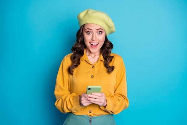 Ritratto di una ragazza allegra positiva e stupita usa lo smartphone goditi il commento di feedback dei social media urla wow omg indossa un copricapo vestito giallo isolato su sfondo blu