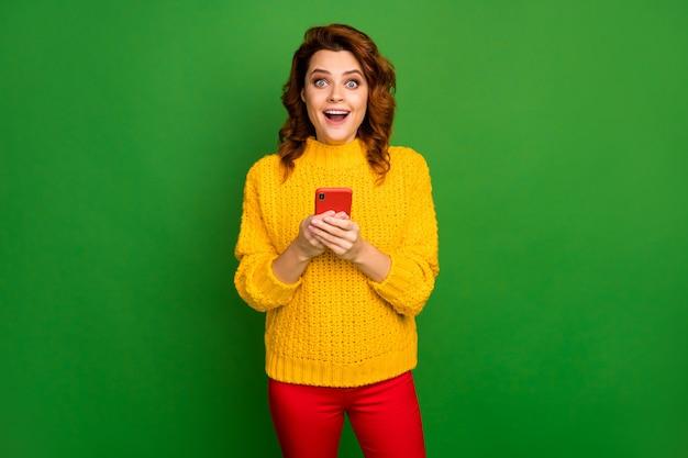 Il ritratto della donna allegra positiva stupita usa il cellulare ha impressionato le notizie della rete dei social media urlare wow omg stile di usura elegante ponticello isolato sopra la parete di colore brillante lucentezza