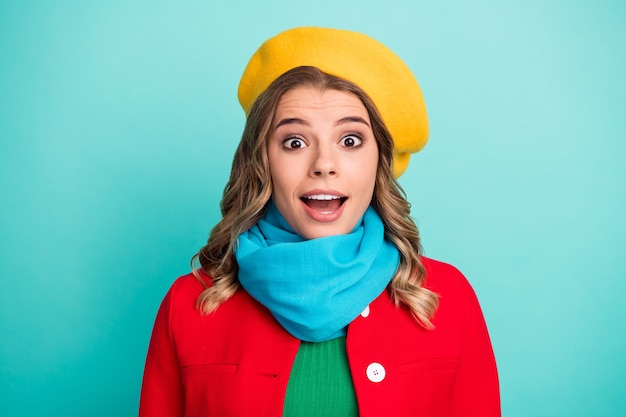 Il ritratto di una ragazza stupita e positiva ha l'aspetto di una passeggiata del fine settimana invernale che ha impressionato le vendite della stagione indossando capispalla luminosi isolati su uno sfondo di colore verde acqua