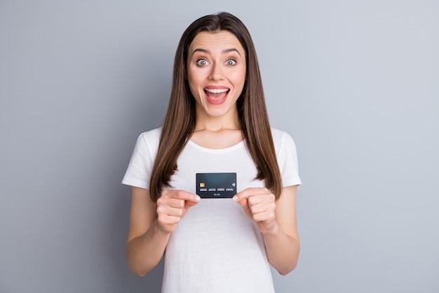 Il ritratto della ragazza positiva stupita tiene la carta di credito impressionata