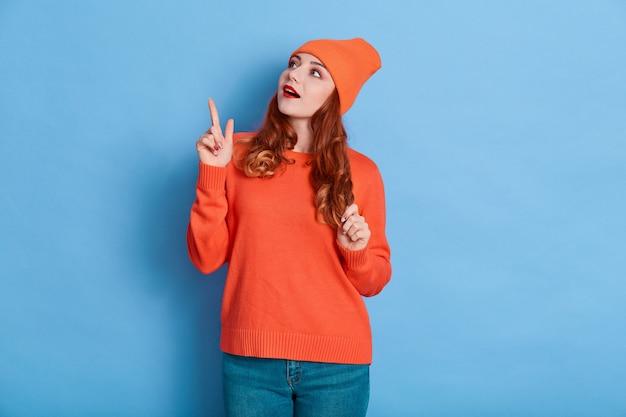 Ritratto di donna stupita punta il dito indice nello spazio della copia, essendo impressionato, indossa maglione, jeans e berretto