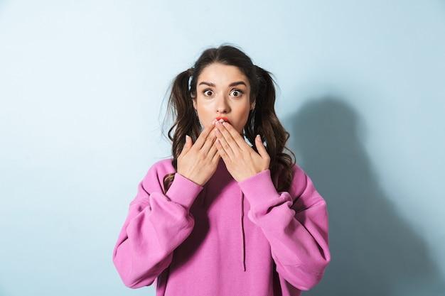 Ritratto di giovane donna stupita con due code di cavallo chiedendosi e coprendosi la bocca con le mani sopra l'azzurro in studio