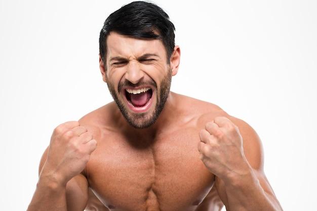 Ritratto di un uomo muscoloso atletico che grida isolato su una parete bianca