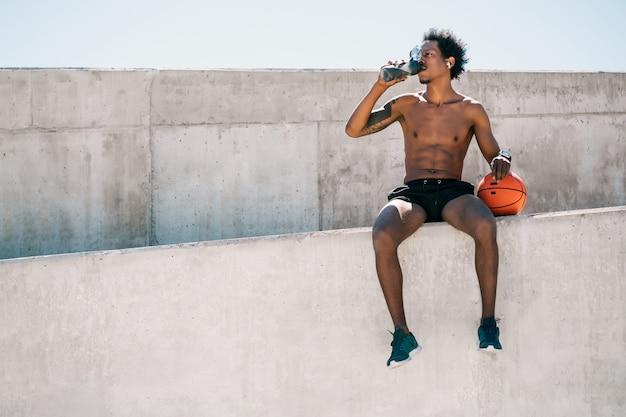 Ritratto di atleta uomo acqua potabile e tenendo la palla da basket all'aperto