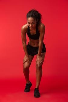 Ritratto di donna afroamericana atletica in abiti sportivi neri in piedi, isolato sopra la parete rossa