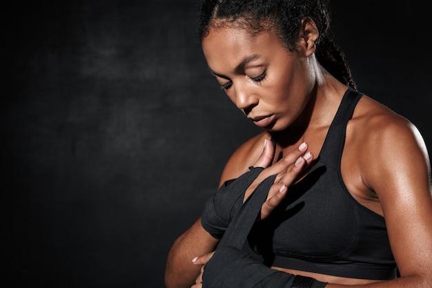 Ritratto di atletica donna afroamericana in abiti sportivi che indossano involucri a mano da boxe isolati su nero