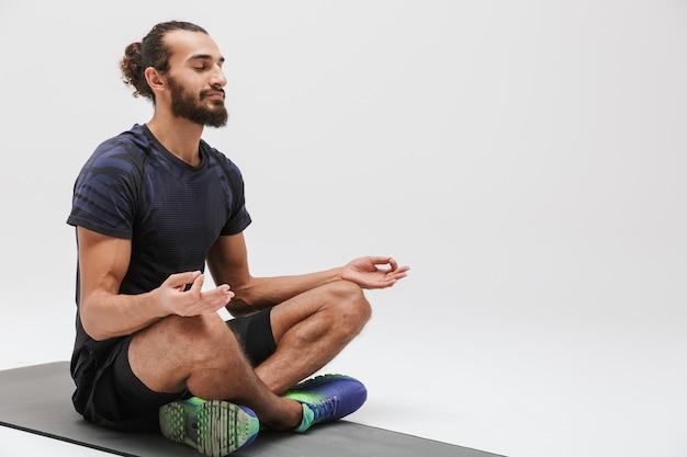 Ritratto di sportivo brunetta atletico in tuta da ginnastica meditando mentre è seduto su un tappetino da yoga isolato su bianco