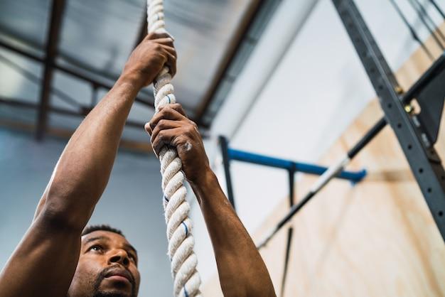 Ritratto di un uomo atletico facendo esercizio di arrampicata in palestra. crossfit, sport e concetto di stile di vita sano.