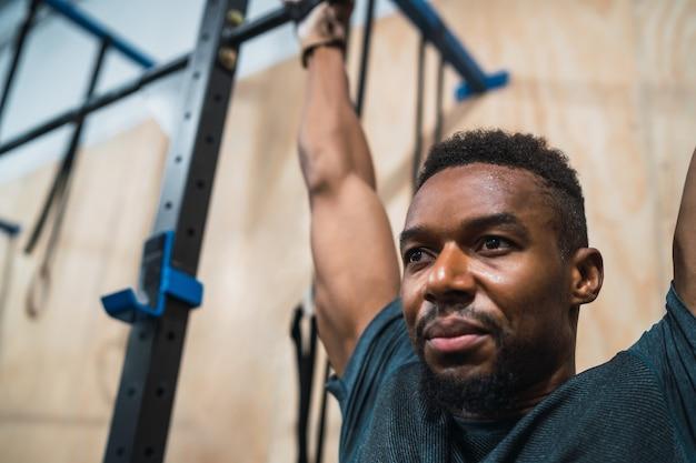 Ritratto di un uomo atletico facendo pull up esercizio in palestra. sport e concetto di stile di vita sano.