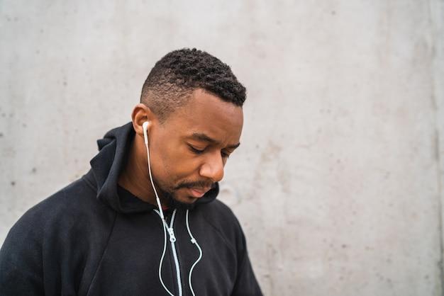 Ritratto di un uomo atletico che ascolta la musica con gli auricolari mentre riposa per l'esercizio, contro il grigio.