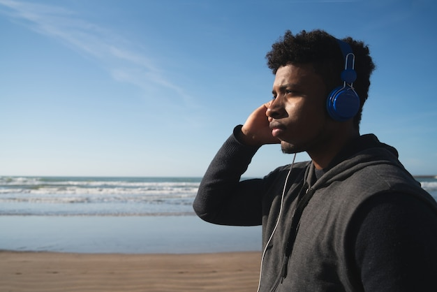 Ritratto di un uomo atletico che ascolta la musica con gli auricolari mentre riposa per l'esercizio in spiaggia. sport e stile di vita sano.