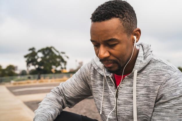 Ritratto di un uomo atletico che ascolta la musica con gli auricolari mentre riposa per l'esercizio.