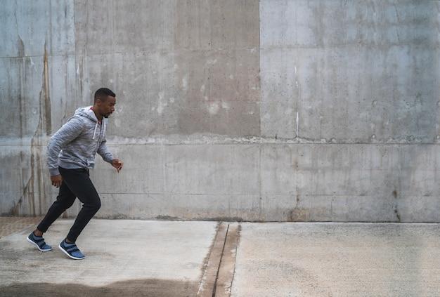 Ritratto di un uomo atletico che corre per strada su sfondo grigio. sport e stile di vita sano.