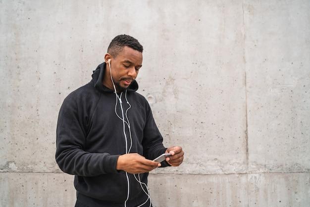 Ritratto di un uomo atletico utilizzando il suo telefono cellulare in una pausa dall'allenamento contro lo spazio grigio. stile di vita sportivo e salutare.
