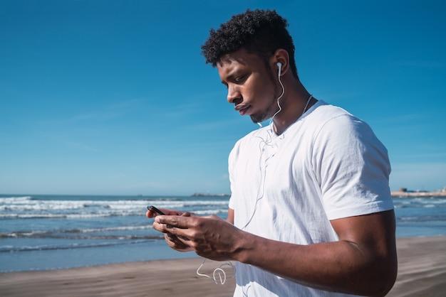 Ritratto di un uomo atletico utilizzando il suo telefono cellulare durante una pausa dall'allenamento sulla spiaggia. stile di vita sportivo e salutare.