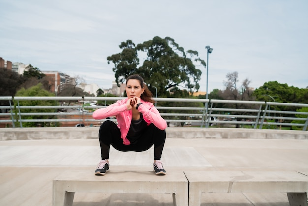 Ritratto di una donna atletica che fa esercizio al parco all'aperto. sport e concetto di stile di vita sano.