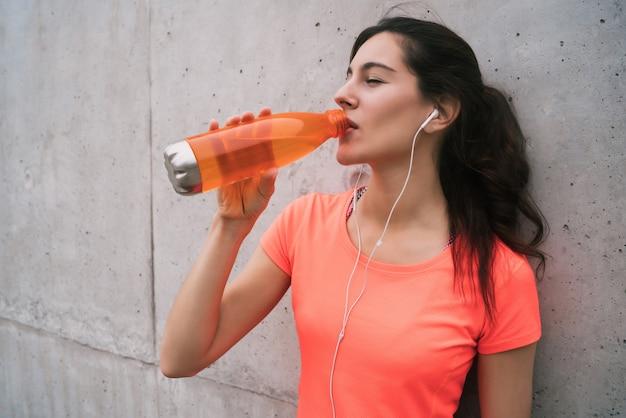 Ritratto di una donna atletica acqua potabile dopo l'allenamento su sfondo grigio. stile di vita sportivo e salutare.