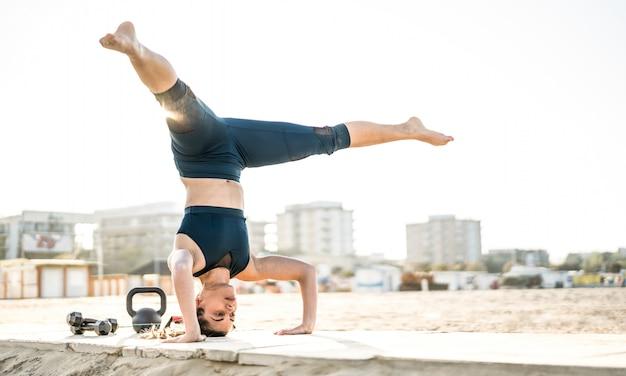 Il ritratto della donna atletica che esercita l'equilibrio calisthenic si muove alla posizione della spiaggia all'aperto