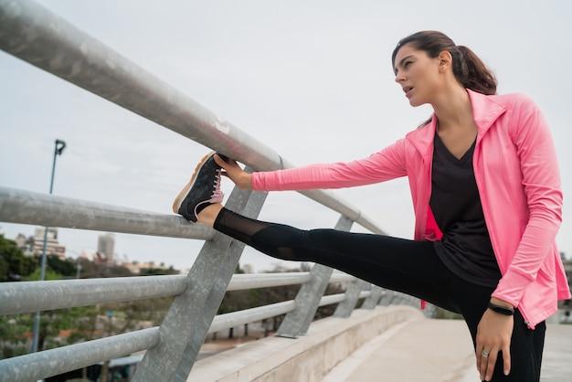 Ritratto di una donna atletica che allunga le gambe prima dell'esercizio all'aperto. sport e stile di vita sano.