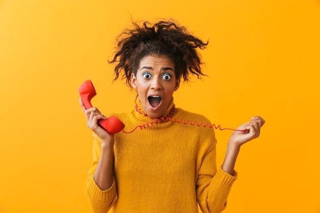 Ritratto di donna afroamericana attraente con acconciatura afro urlando mentre si tiene il microtelefono rosso, isolato