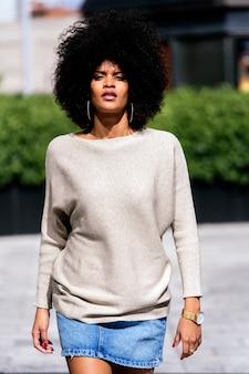 Ritratto di donna afro attraente in strada. concetto di stile di capelli