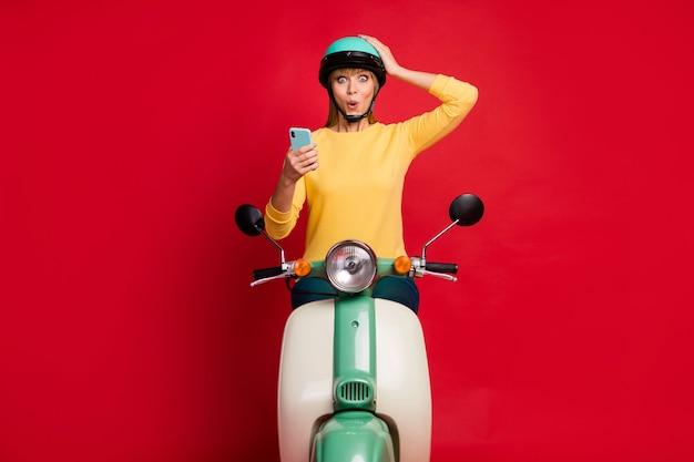 Ritratto della ragazza allegra stupita attraente che si siede sul ciclomotore facendo uso delle notizie della lettura delle cellule